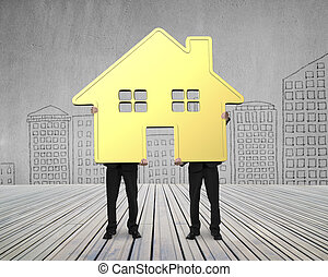 Two businessmen holding gold house together