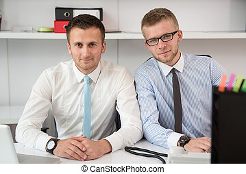 Two Businessmen In An Office Smiling