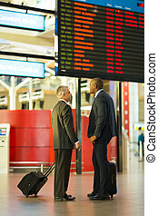 businessmen in front of airport information board