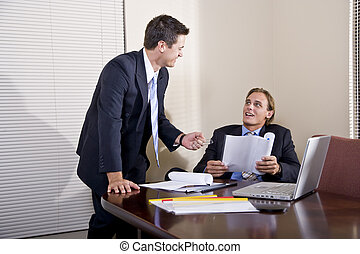 Two businessmen in suits working together in boardroom