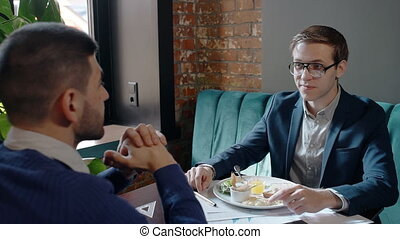 Two businessmen is talking during business lunch, sitting at table in cafe.