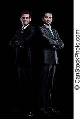 two businessmen isolated over black background.