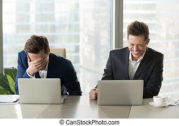 Two businessmen laughing out loud at workplace, office workers screaming with laughter and can not stop, funny positive emotions at work, cheerful colleagues having fun sitting at desk with laptops