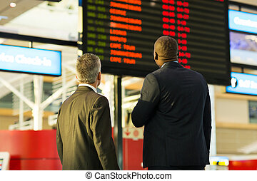 businessmen looking at flight information board