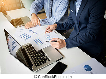 Two businessmen looking at report and having a discussion in office. business concept.