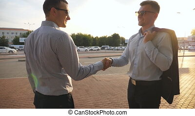 Two businessmen meeting at city street and greeting each...