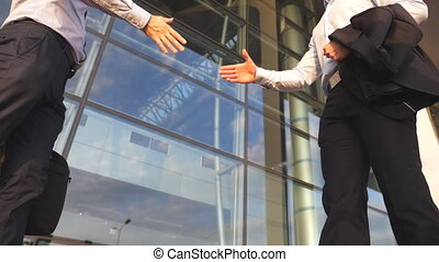 Two businessmen meeting near office building and greeting...