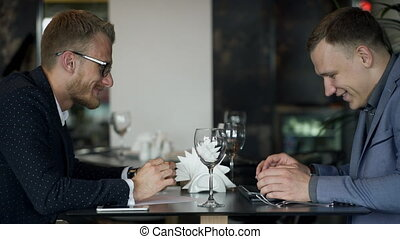 Two businessmen meets for discussion questions in their lunch in the cafe.