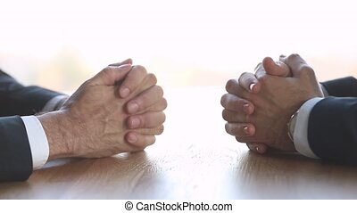 Two businessmen negotiators with clasped male hands...