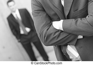 two businessmen one standing in front of the other with the first folding his arms and the second with hands in pockets