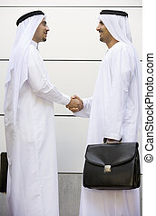 Two businessmen outdoors shaking hands and smiling