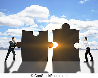 Two businessmen pushing puzzle pieces together on sky background with setting sun. Cooperation concept