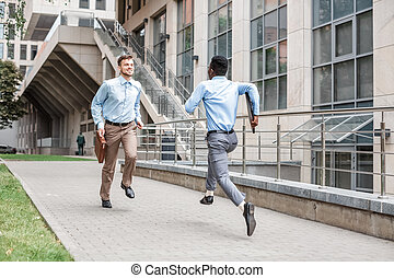 two businessmen running to meet each other