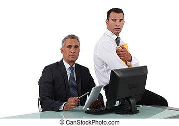 Two businessmen sat at desk