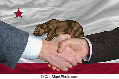 two businessmen shaking hands after good business investment agreement in america, in front US state flag of california