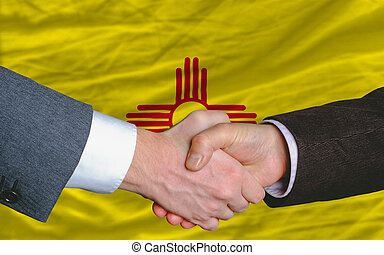 two businessmen shaking hands after good business investment agreement in front US state flag of new mexico