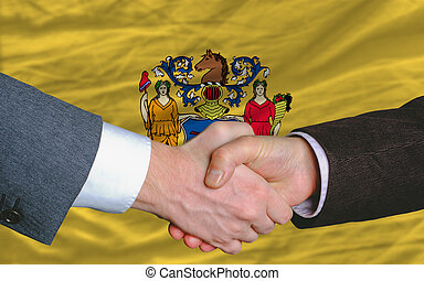 two businessmen shaking hands after good business investment agreement in front US state flag of new jersey
