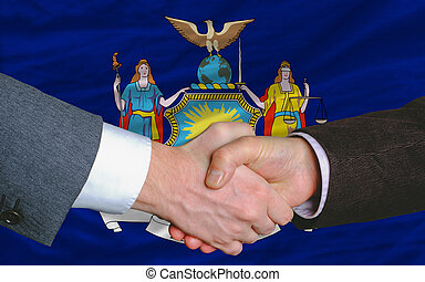 two businessmen shaking hands after good business investment agreement in front US state flag of new york