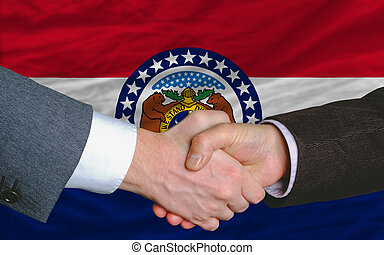 two businessmen shaking hands after good business investment agreement in front US state flag of missouri