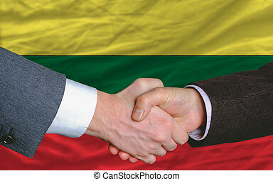 two businessmen shaking hands after good business investment agreement in lithuania, in front of flag