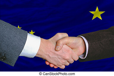 two businessmen shaking hands after good business investment agreement in front US state flag of alaska