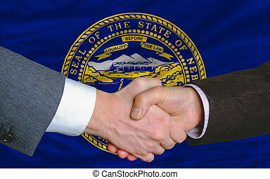 two businessmen shaking hands after good business investment agreement in front US state flag of nebraska