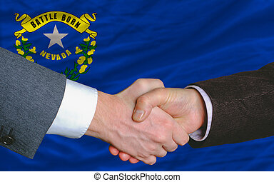 two businessmen shaking hands after good business investment agreement in front US state flag of nevada