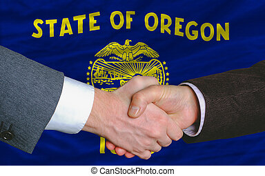 two businessmen shaking hands after good business investment agreement in front US state flag of oregon