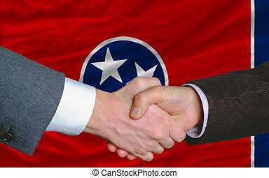 two businessmen shaking hands after good business investment agreement in front US state flag of tennessee