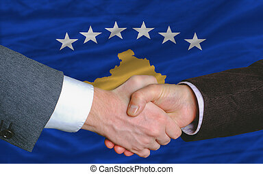 two businessmen shaking hands after good business investment agreement in front of flag of kosovo