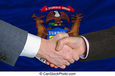 two businessmen shaking hands after good business investment  agreement in front US state flag of michigan