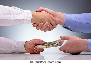 Two Businessmen Shaking Hands And Receiving Bribe