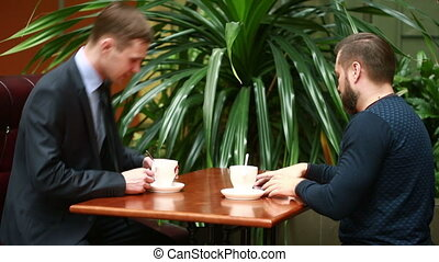 Two businessmen shaking hands in a cafe