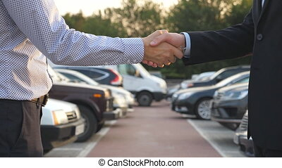 Two businessmen shaking hands of each other with cars in...