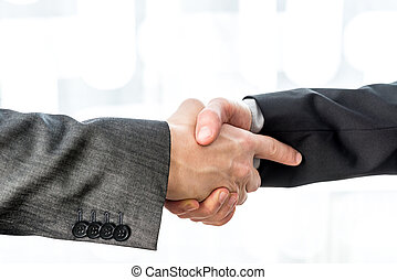 Two businessmen shaking hands over a blurred abstract background
