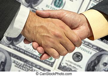 Two businessmen shaking hands - handshaking on the money...