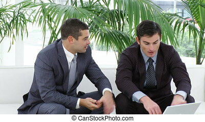 Two businessmen sitting on sofa using a laptop