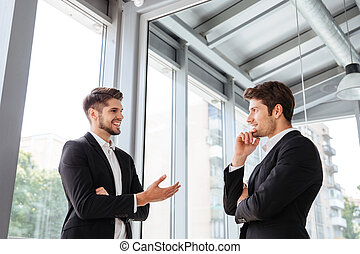 Two businessmen smiling and talking in office