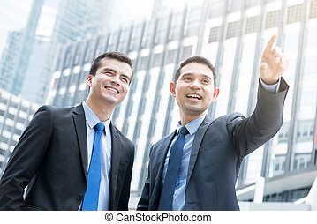 Two businessmen standing outdoors in the city
