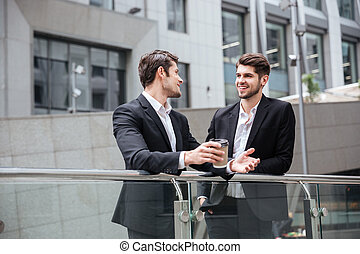 Two businessmen talking and drinking coffee in the city