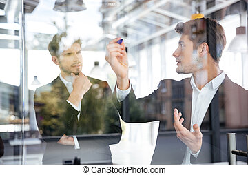 Two businessmen talking and writing on glass board in office