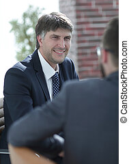 Two businessmen talking in the boardroom.