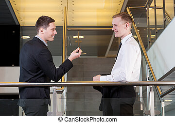 Two businessmen talking to each other - Two young...