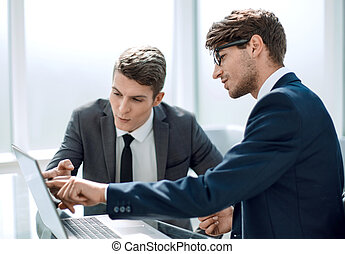 two businessmen use a laptop in the office