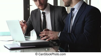 Two businessmen wear suits discuss online strategy point at laptop.