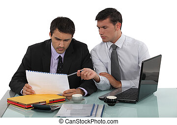 Two businessmen working on a project.