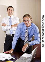 Two businessmen working together in boardroom