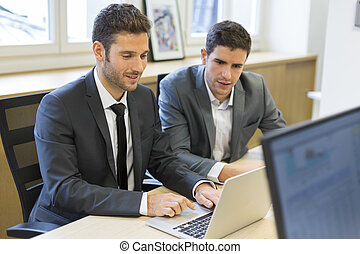 Two businessmen working together on a project in the office