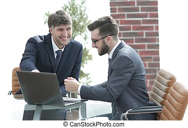 Two businessmen working together using laptop on business meeting in office