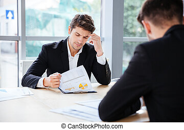 Two businessmen working with business plan in office